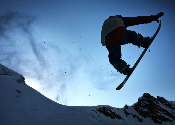 Silhouette snowboarder jumping high in the air